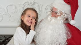 Sweet little girl on Santa Claus lap telling him what she wants for Christmas stock photography