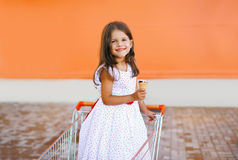 Sweet little girl in shopping cart. With icecream Stock Images