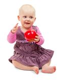 Sweet little girl sits with an apple in his hand Royalty Free Stock Images