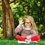 Sweet little girl sits in a park. Reading book and hand gesture w Stock Image
