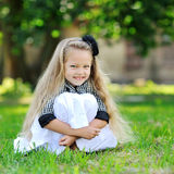 Sweet little girl sitting in a grass and smiling Stock Photo