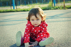 Sweet little girl sitting on the ground outdoor. Cute baby with curly hair looking at camera. Stock Photo