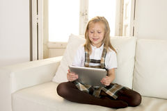 Sweet little girl sitting on home sofa couch using internet app on digital tablet pad Stock Photo