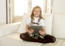 Sweet little girl sitting on home sofa couch using internet app on digital tablet pad Royalty Free Stock Photos