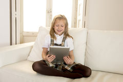 Sweet little girl sitting on home sofa couch using internet app on digital tablet pad Royalty Free Stock Image
