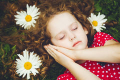 Sweet little girl sleeping on the grass with chamomiles. Stock Photo