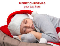 Sweet little girl sleeps in Santa caps. Stock Photos