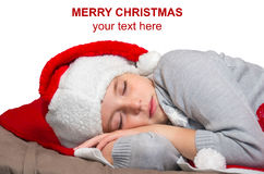 Sweet little girl sleeps in Santa caps. Royalty Free Stock Images