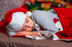 Sweet little girl sleeps in Santa caps. Stock Photography