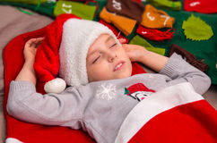 Sweet little girl sleeps in Santa caps. Royalty Free Stock Photography
