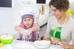 Sweet little girl sprinkle. Flour in kitchen Royalty Free Stock Photography
