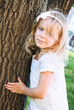 Sweet little girl standing at the park near a tree Royalty Free Stock Photo