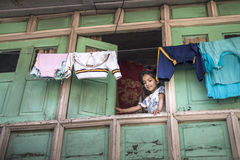 Sweet little girl stare down from her wooden house window with hanging clothes at top. Royalty Free Stock Photos