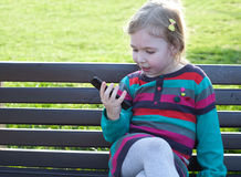 Sweet little girl using a smart phone in a city park sitting on a bench Royalty Free Stock Image