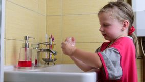 Sweet little girl washes her hands in the bathroom. Preschool concept, childhood concept. Cute girl wears nightdress.  stock footage