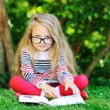 Sweet little girl wearing glasses and reading book in a park Stock Photos