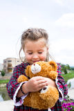 Sweet little holding teddy bear in her arms. Portrait of pretty little girl, 3 years old hugging her teddy bear in the city Royalty Free Stock Photography