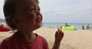 Funny child on beach. Sweet little kid frowning and looking away while standing on sandy beach near sea stock video