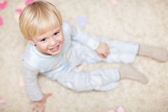 Sweet little kid sitting on the floor Royalty Free Stock Images