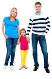Sweet little kid standing in between her parents Stock Photos