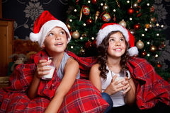 Sweet little kids drinking milk in the bed royalty free stock photos