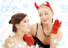 Sweet little lie. Picture of angel and devil girls with snowflakes royalty free stock image