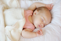 Sweet little newborn baby in a bed stock image