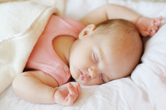 Sweet little newborn baby in a bed stock photography