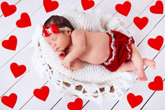 Sweet little newborn baby is sleeping on the background with hearts. Royalty Free Stock Images