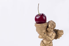 Sweet little pink angel statue with cherry (white studio background) Stock Photography