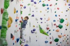 Sweet little preschool boy, climbing wall indoors. Having fun, active children royalty free stock photos