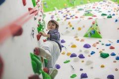 Sweet little preschool boy, climbing wall indoors. Having fun, active children stock images