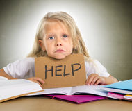 Sweet little school girl holding help sign in stress with books Stock Images