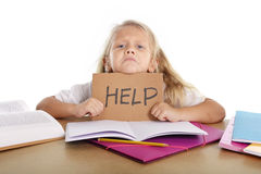 Sweet little school girl holding help sign in stress with books and homework Royalty Free Stock Photo