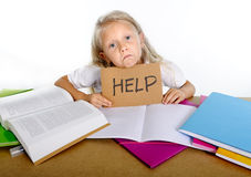 Sweet little school girl holding help sign in stress with books and homework. Sweet little blonde hair school girl holding help sign in stress with books and Royalty Free Stock Photography