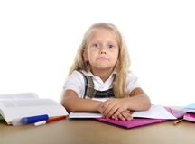 Sweet little school girl tired and sad in stress with books and homework Stock Photography