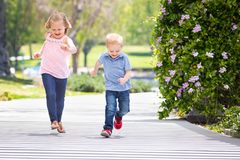 Sweet Little Sister and Brother Having Fun Running At The Park Royalty Free Stock Photography