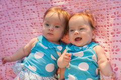 Sweet little  twins lying on a pink blanket. They in blue dress with white polka dots Stock Images