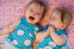 Sweet little  twins lying on a pink blanket. They in blue dress with white polka dots Stock Photos