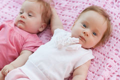 Sweet little  twins lying on a pink blanket. They in pink and white dresses Stock Photo