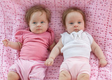 Sweet little  twins lying on a pink blanket. They in pink and white dresses Royalty Free Stock Images