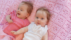 Sweet little  twins lying on a pink blanket. They in pink and white dresses Royalty Free Stock Photography