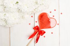 Sweet lolly heart on stick with bow with white flowers. Over white wooden background Stock Images