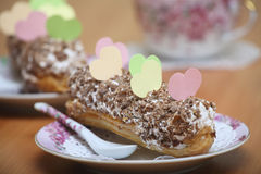 Sweet love valentine. Served eclairs for a couple on a wooden table with paper hearts Royalty Free Stock Image