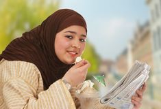 Sweet lunch. Young islamic woman enjoying ice cream in the sunshine Stock Photos