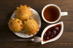 Sweet lush cupcake with strawberry jam and tea. In white dish on wooden table Stock Photo
