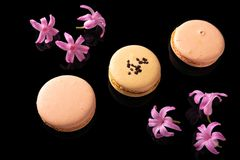 Sweet macarons or macaroons. Decorated with blooming flowers on a black background stock image