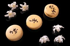 Sweet macarons or macaroons. Decorated with blooming flowers on a black background royalty free stock images