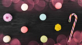 Sweet macarons on wooden table, flowers and lollipop royalty free stock photos