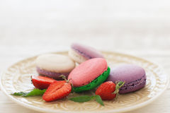 Sweet macaroons with strawberry on plate copyspace. Sweet colorful macaroons with strawberry slices on plate copyspace. Front view on white glass plate with stock photo